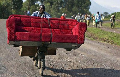 uomo trasporta un divano in bicicletta