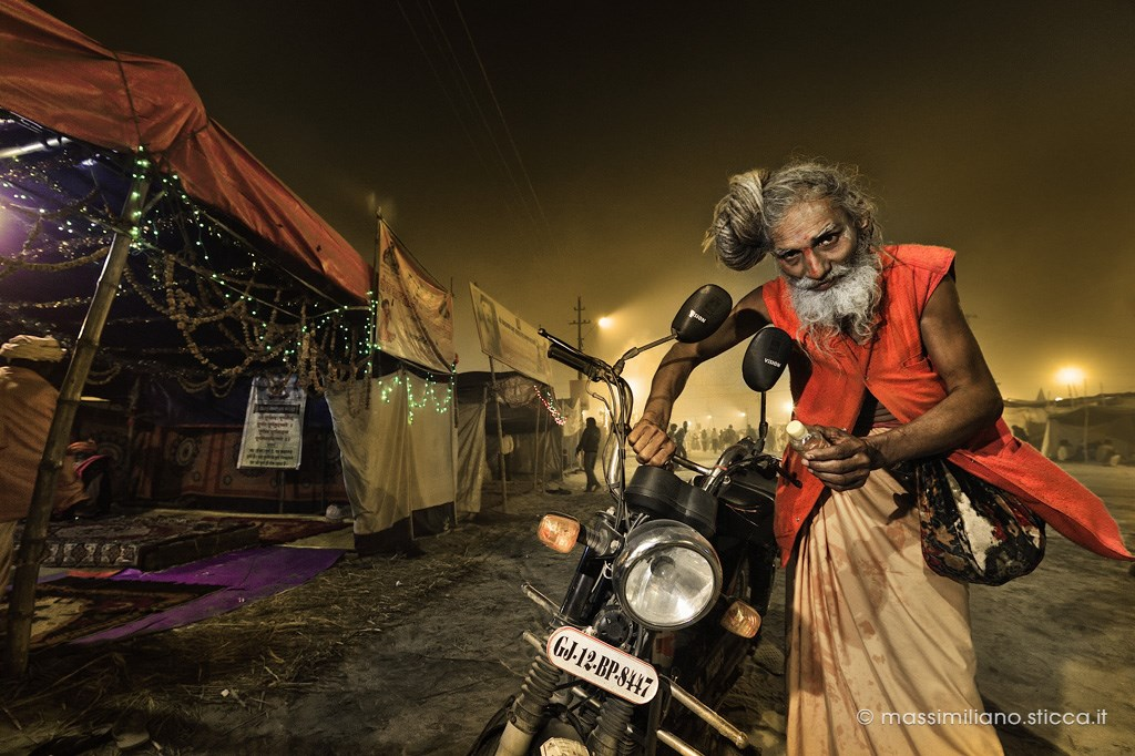 A Naga Sadhu with his motorbike, near a tent in Kumbh Mela
