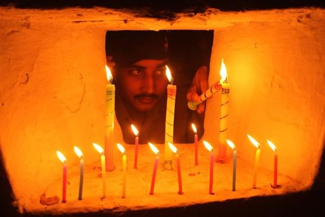 un militare accende una candela per il diwali